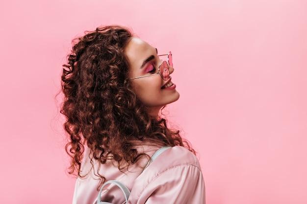 Senhora positiva em jaqueta de seda posando em fundo rosa