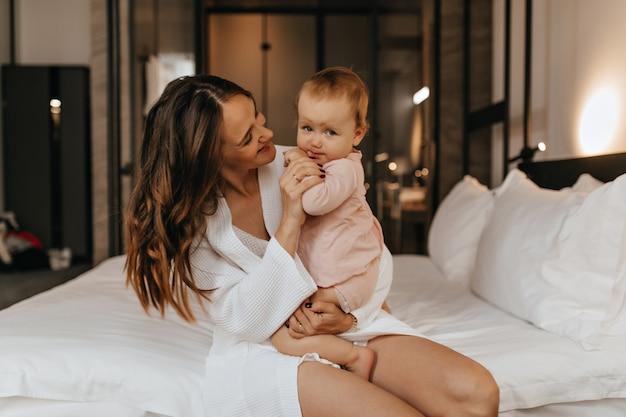 Senhora positiva em roupão de banho, sentada na cama branca e brincando com um lindo bebê loiro sorridente.