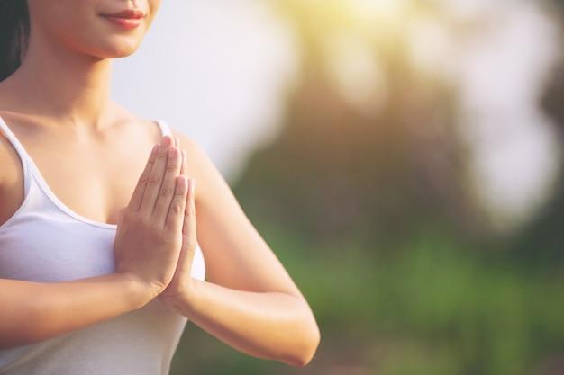 Senhora praticando ioga no parque ao ar livre, meditação.