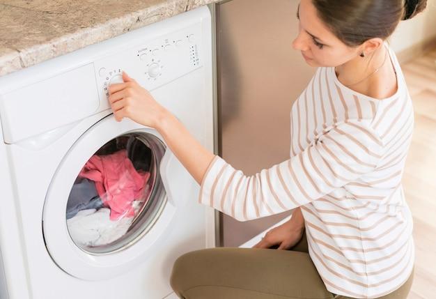 Senhora que escolhe o programa na máquina de lavar roupa