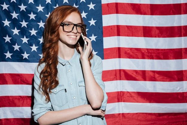 Senhora ruiva alegre em pé sobre a bandeira dos eua falando por telefone.