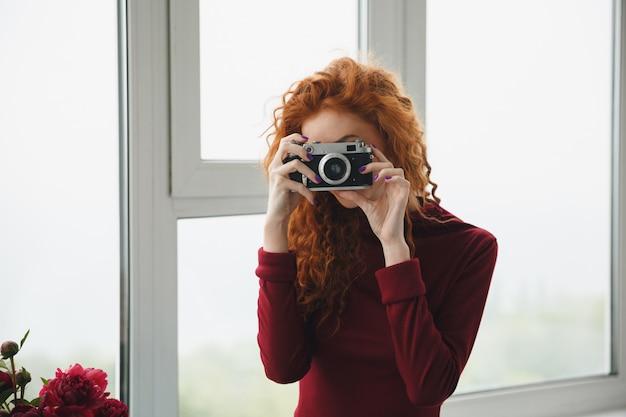 Senhora ruiva dentro de casa perto de flores, segurando a câmera.