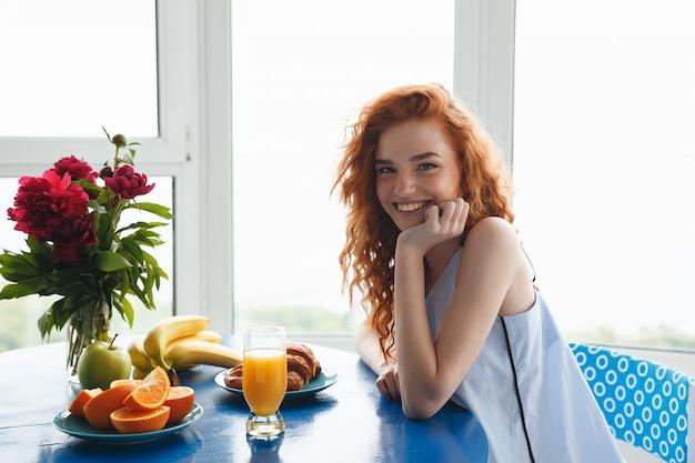 Senhora ruiva jovem muito alegre perto de flores e frutas