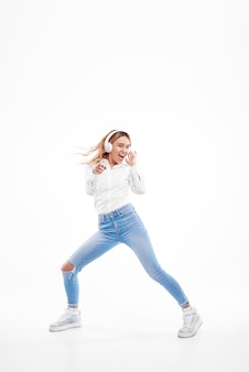 Senhora ruiva linda ouvindo música no rádio em fones de ouvido e pulando alto. menina encantadora em roupas casuais e fones de ouvido dançando com cabelo acenando em branco