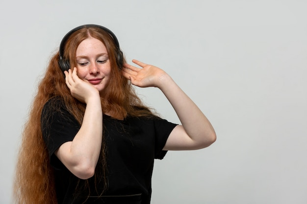 Senhora ruiva ouvindo música de vestido preto na cinza