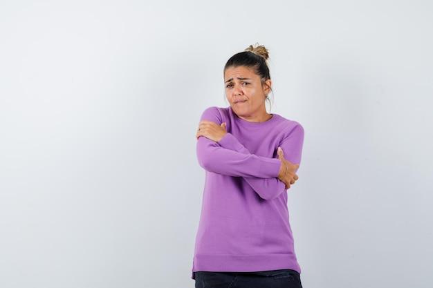 Senhora se abraçando em uma blusa de lã e parecendo indefesa