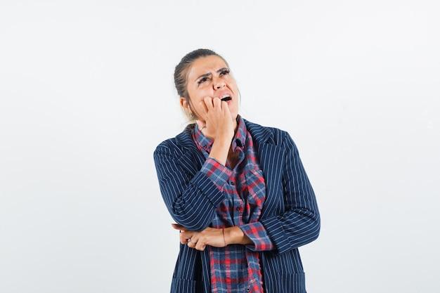 Senhora segurando a mão na bochecha em camisa, jaqueta e olhando pensativa, vista frontal.