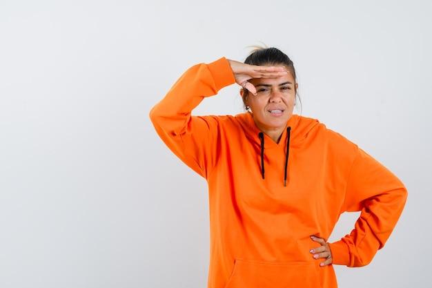 Senhora segurando a mão na cabeça com um capuz laranja e olhando focada