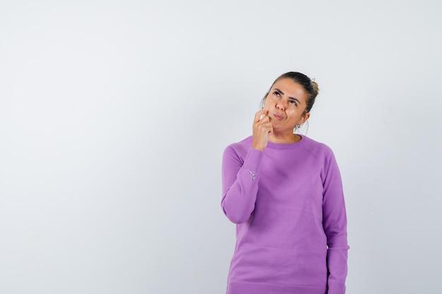 Senhora segurando a mão no queixo com blusa de lã e parecendo indecisa