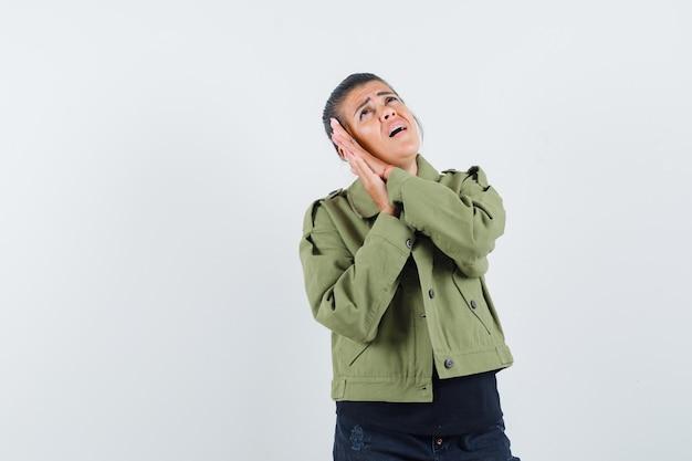 Senhora segurando as mãos como travesseiro na jaqueta