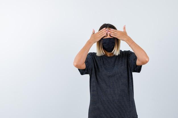 Senhora segurando as mãos nos olhos no vestido preto, máscara médica e parecendo animada, vista frontal.
