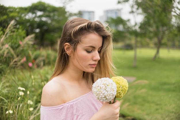 Senhora segurando flores brilhantes no parque da cidade