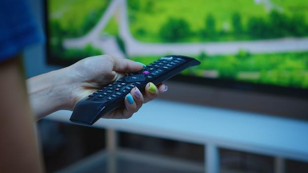 Senhora segurando o controle remoto da tv e pressionando o botão. close-up de uma mão de mulher mudando os canais de tv, sentada em um sofá confortável em frente à televisão, usando o controle para escolher um filme