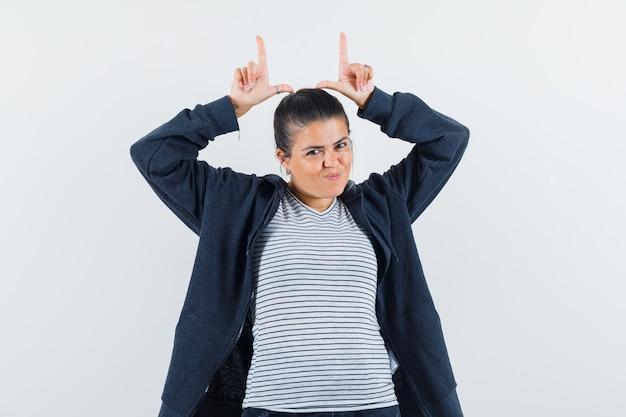 Senhora segurando os dedos acima da cabeça em uma camiseta