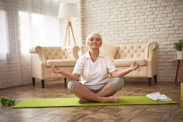 Senhora sênior ativa em lotus pose yoga meditation.