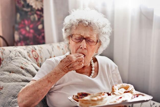 Senhora sênior, degustação de uma sobremesa
