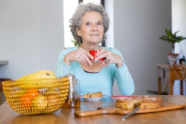 Senhora senior positiva, desfrutando de torta saborosa