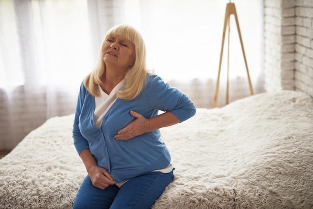 Senhora sênior que sofre o tratamento urgente da dor de coração.