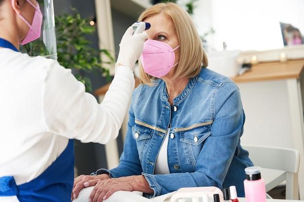 Senhora sênior usando máscara em salão de manicure