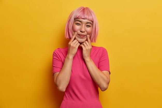 Senhora sensual e positiva com cabelo rosa, mantém os dedos perto dos cantos da boca, força o sorriso, finge estar de bom humor