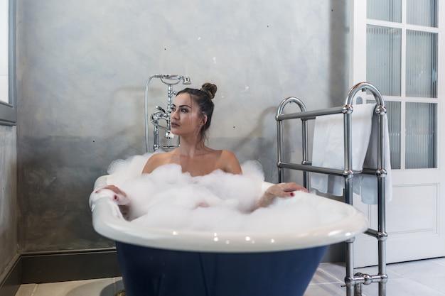 Senhora sensual tomando banho e olhando para longe