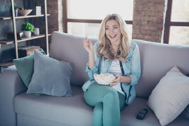 Senhora sentada no divã comendo pipoca assistindo tv