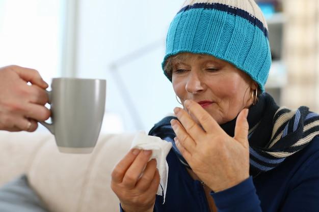 Senhora sentada no sofá beber retrato de chá