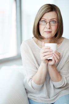 Senhora sentada no sofá com uma xícara de café