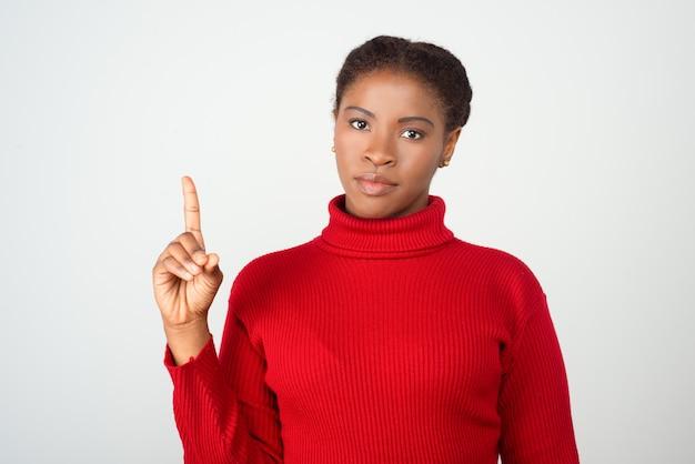 Senhora séria apontando o dedo indicador para cima