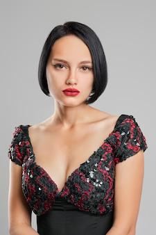 Senhora séria com cabelo escuro curto e lábios vermelhos posando no estúdio