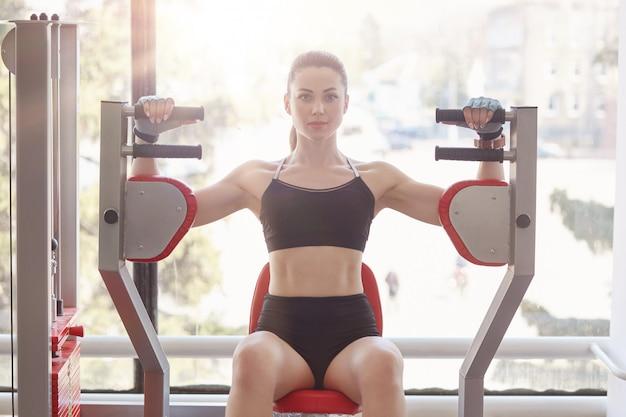 Senhora séria com físico malhando na estação de fitness, vestindo sutiã esportivo preto e fêmea curta e atraente com rabo de cavalo, desenvolvendo força ao treinar bíceps no ginásio.