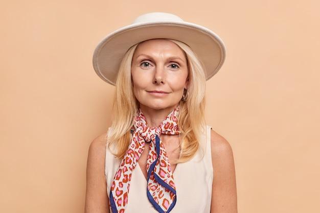 Senhora séria e feminina com cabelos claros, maquiagem mínima, vestida com uma camiseta branca, chapéu e lenço amarrado no pescoço, fazendo poses de caminhada em ambientes fechados contra a parede bege