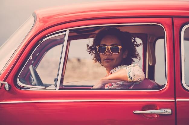 Senhora séria em um velho carro vermelho bonito retrô olhando para você com o vidro da janela aberta