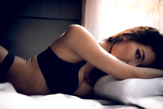 Senhora sexy asiática com peito grande em biquíni preto