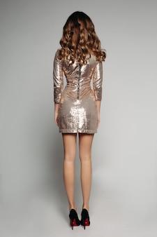 Senhora sexy com cabelo moreno brilhante, vestido cintilante dourado para sair à noite e saltos.