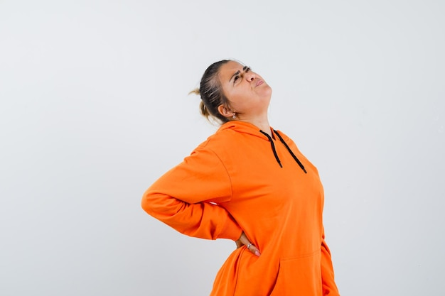 Senhora sofrendo de dor nas costas, usando um capuz laranja e parecendo cansada