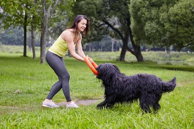 Senhora sorridente brinca com briard em parque público.
