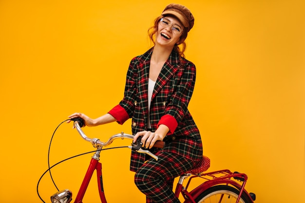 Senhora sorridente com jaqueta xadrez andando de bicicleta