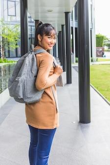 Senhora sorridente com mochila e documentos