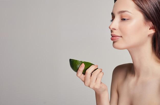 Senhora sorridente com pele de brilho puro perfeito com abacate na mão