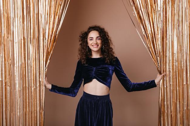 Senhora sorridente com roupa azul escura posando no fundo de cortinas douradas
