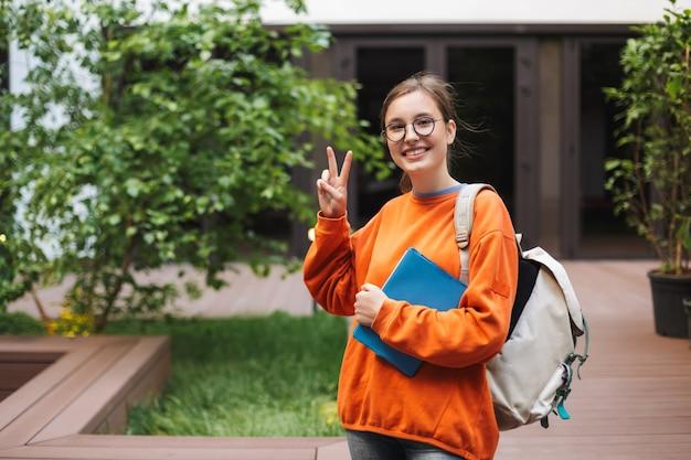 Senhora sorridente de óculos em pé com uma mochila e feliz mostrando o gesto de dois dedos enquanto