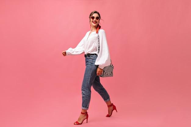 Senhora sorridente em jeans, blusa branca andando sobre fundo rosa. mulher elegante em passos de óculos de sol vermelhos no pano de fundo isolado.