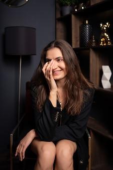 Senhora sorridente em mini saia e jaqueta preta de grandes dimensões, sentado na poltrona moderna na sala