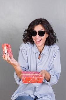 Senhora sorridente em óculos de sol com presentes