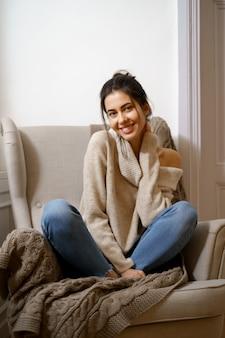 Senhora sorridente em roupas da moda inteligente está sentada na poltrona. sorrindo, sentado em uma atmosfera relaxante dentro de casa