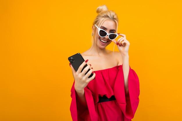 Senhora sorridente em um vestido vermelho detém óculos no rosto enquanto segura um telefone em uma superfície amarela com espaço de cópia
