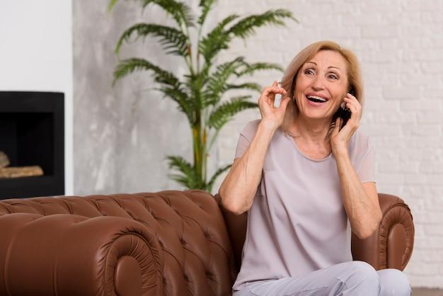 Senhora sorridente, falando ao telefone