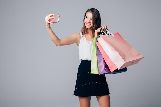 Senhora sorridente fazendo selfie em seu telefone com sacolas de compras em fundo branco e sacolas de papel nos braços