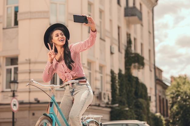 Senhora sorridente na bicicleta, mostrando um gesto de paz para uma selfie. banner modelo